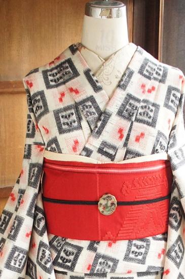 生成り色の地に赤のキューブドットと黒の四角モチーフが織り出され、変わり市松模様を描き出すレトロモダンなウールの単着物です。