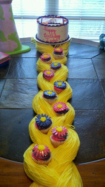 """izzy's cake for tangled party.  the cake was made by """"sweet confections"""" as were the cupcakes.  i added the yarn braid!"""