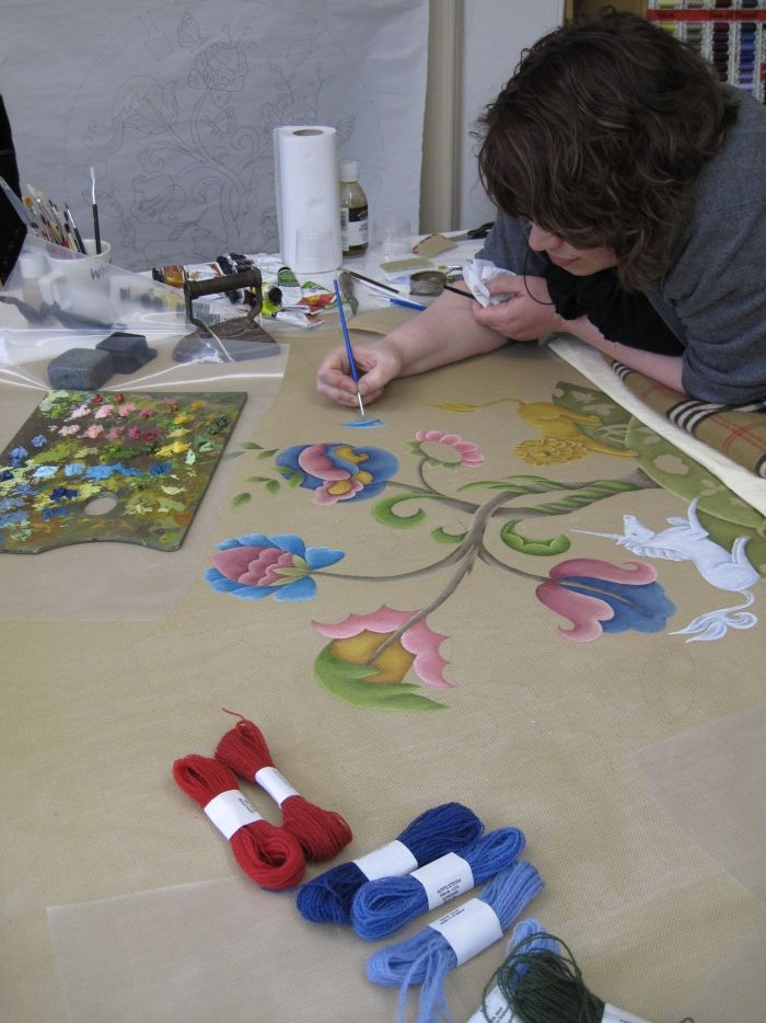 Paintng on an open grid canvas takes longer that painting on paper. The canvas needs to be made flat with a hand iron (visible in the background). Image courtesy The Royal School of Needlework, London.