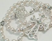 White Pearl Bridal Rosary •Decade beads classic Swarovski White Pearls (8mm) •Our Father beads are stunning Faceted Clear glass with Silver overlay accented with Bali Daisy beads •Silver with Brite-Cut center round spacer beads throughout compliment the beauty of this piece •This Piece is shown with Crystal Encrusted Cross and Swarovski Clear Crystal Center Flower