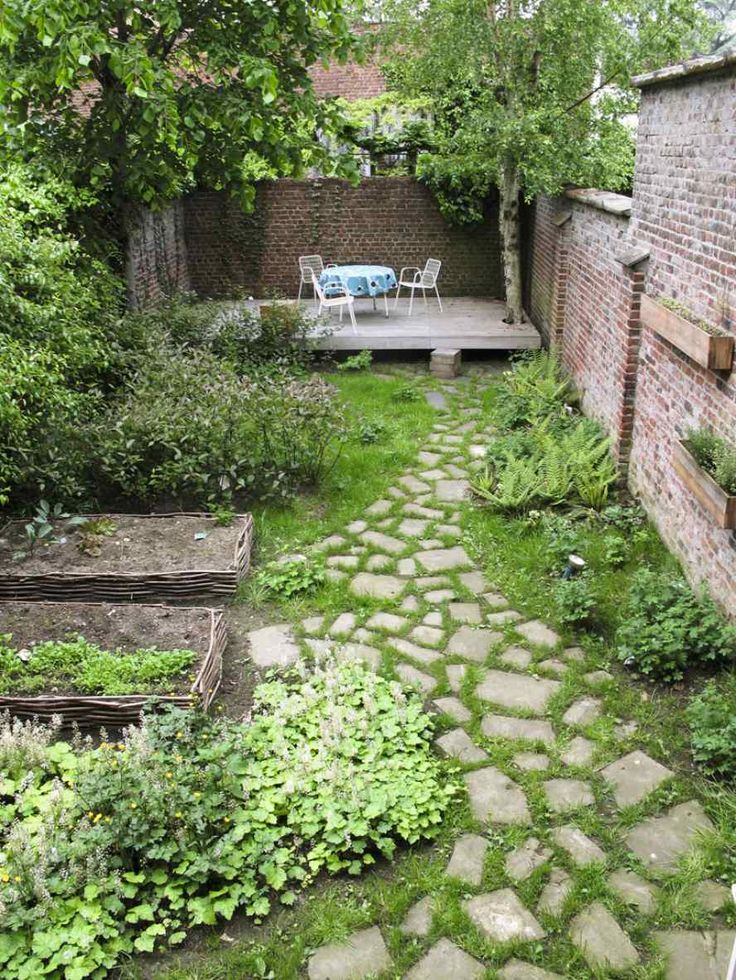 small narrow garden with a deck a lovely path and veg patch