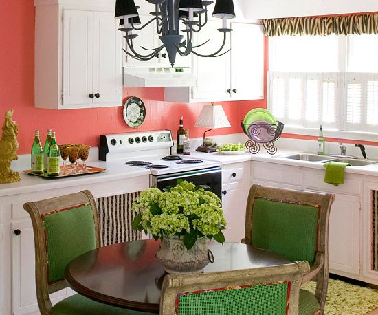 Coral + Kelly Green An impressionistic canvas presents all the colors needed to give this kitchen a whimsical attitude. Warm coral walls, cool green upholstered chairs, and a chartreuse area rug offer vibrant color, while white cabinets and black accents keep the tropical palette from overwhelming the space. Striped fabric on a valance and cabinet-door inserts adds a fun pattern to the mix.