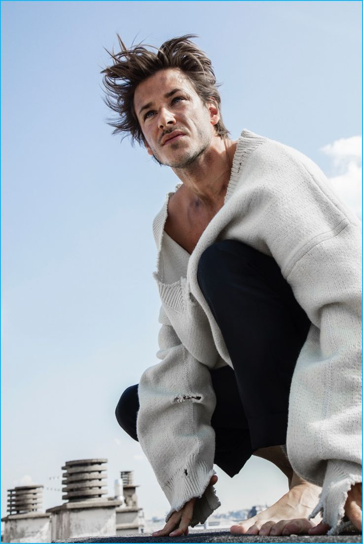 Gaspard Ulliel pictured in a distressed oversized v-neck sweater from Raf Simons…