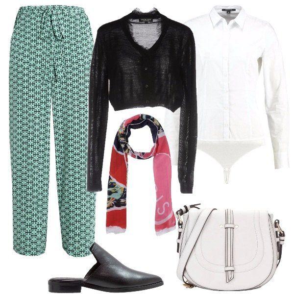 Outfit composto da pantaloni a fantasia, camicia bianca, cardigan nero lavorato a maglia leggera, ciabattine nere in pelle, borsa a tracolla bianca in ecopelle e foulard a fantasia.