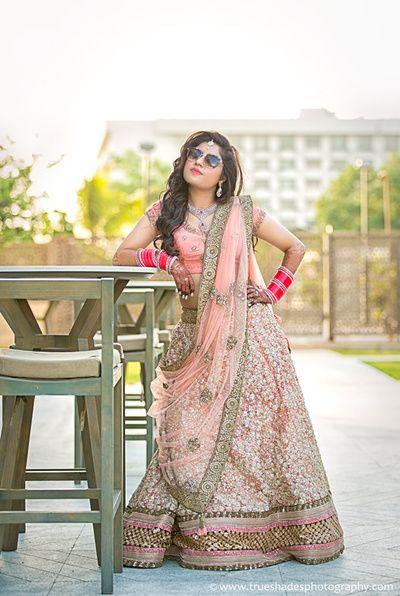 bride wearing aviators, pastel pink lehenga, sequins work, gold broder, copper…