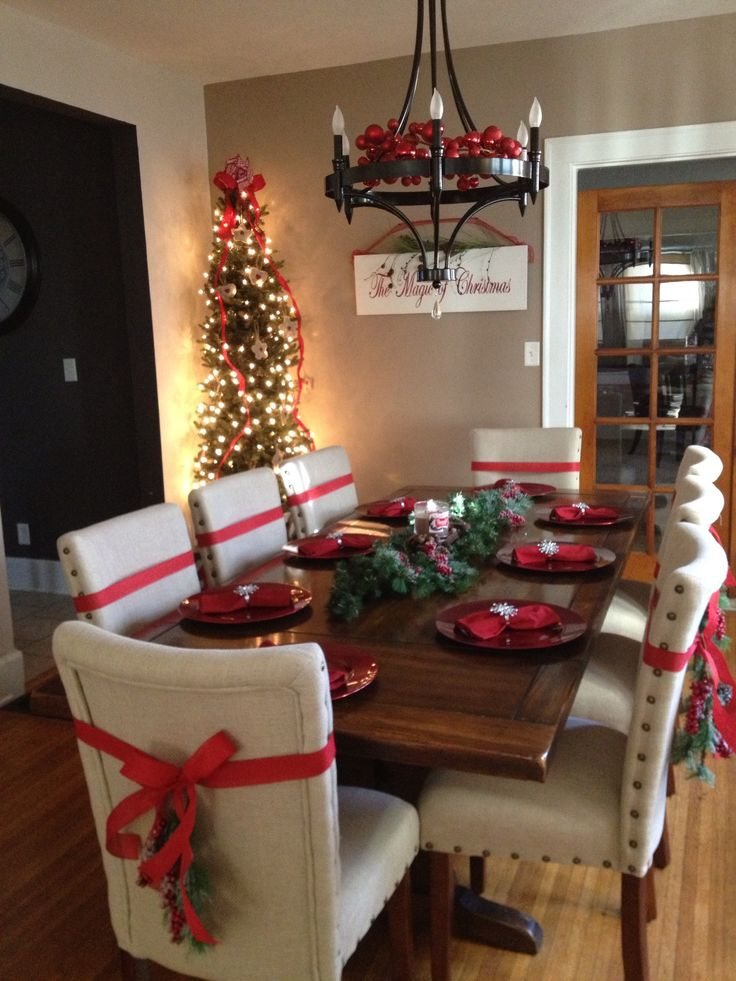 Dinning room for the Holidays. Tree in dinning room. Ribbons on chairs. White…