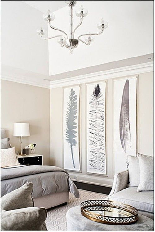 A monochromatic, and very modern bedroom, draws on the animal magnetism and beauty of feathers. Glistening silver and gold accents, from the chandelier, lamp and serving tray, add a touch of sophistication.