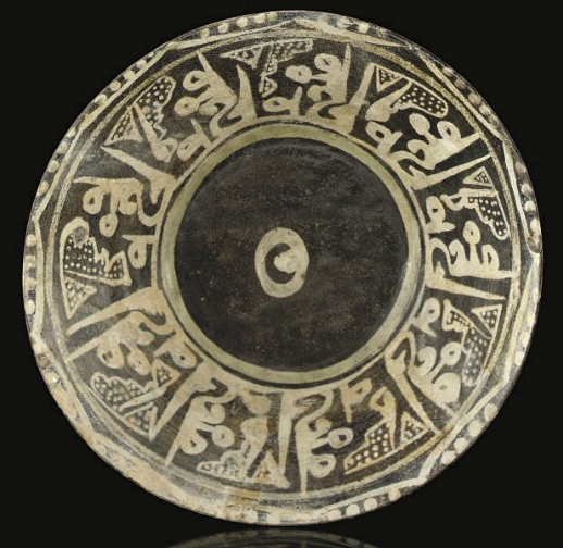 A SLIP PAINTED POTTERY BOWL, NISHAPUR OR SAMARKAND, 10TH CENTURY Of flaring conical form on short foot, painted in white and yellow slip on a brown ground with a wide band of pseudo-kufic, the exterior with graduated dashes - 8 1/8in (20.5cm) diameter