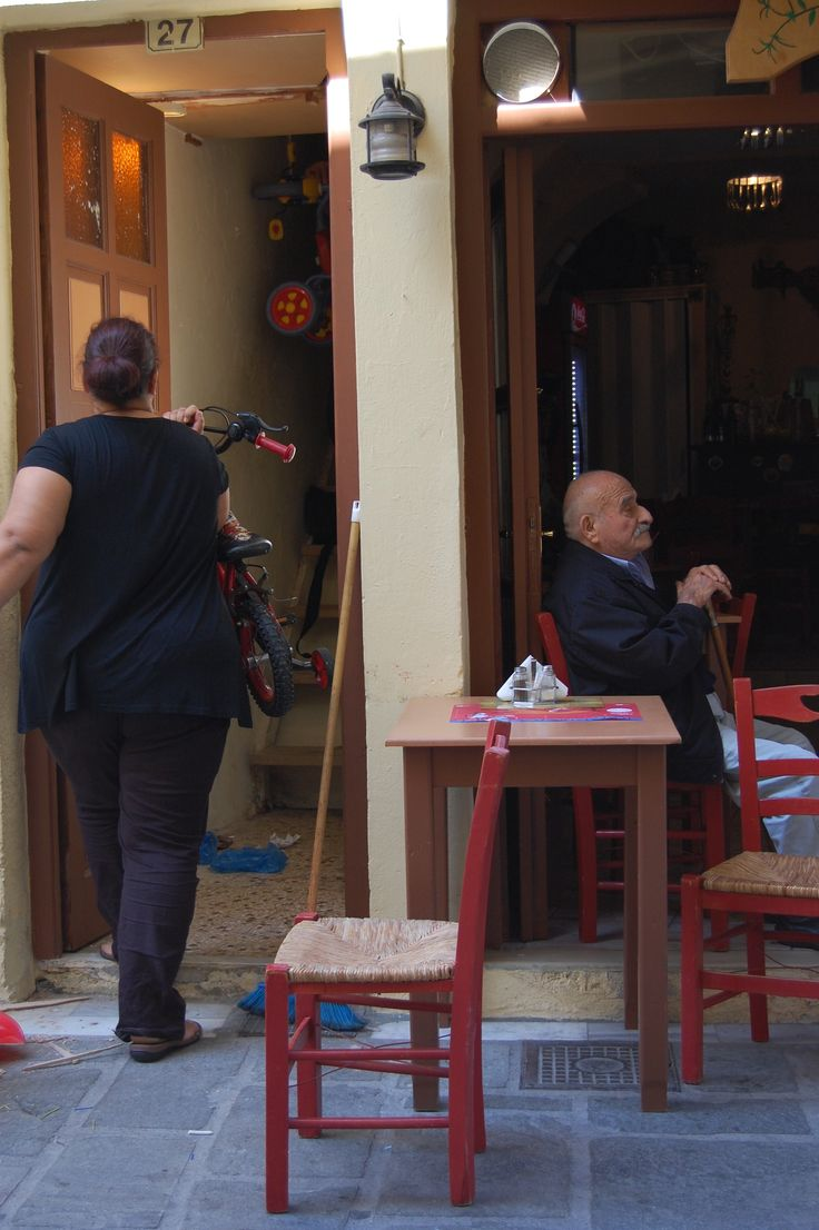 A parked husband and a housewife cleaning the stairway, Crete