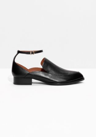 Leather loafers with a dressy menswear-inspired look featuring scuplted sides, pointy toes and feminine ankle straps.