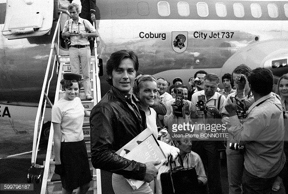 Alain Delon et Romy Schneider entourés de photographes à leur arrivée à l'aéroport de Nice en septembre 1968, en France .