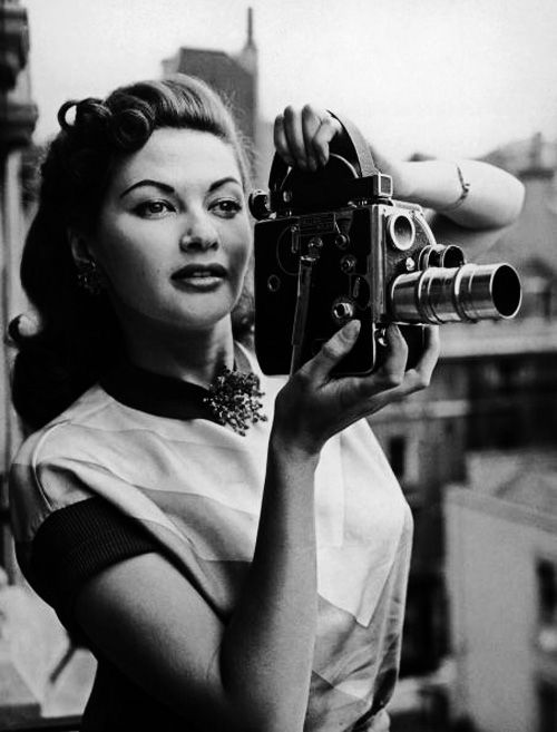 Yvonne De Carlo using a Bolex cine camera to film from her suite at the Washington Hotel, London, 6th August 1952. Photo by FGP / Hulton Archive / Getty Images. °