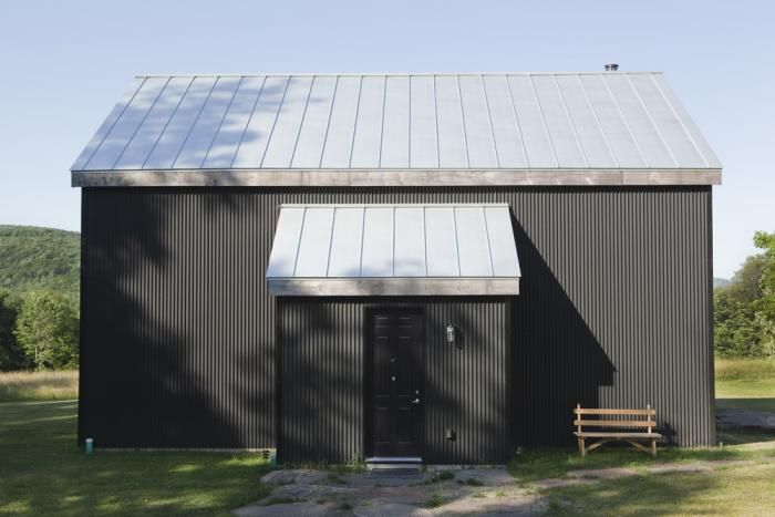 The exterior of the 19th-century barn is clad in black corrugated aluminum. The standing seam aluminum roof is typical of the vernacular architecture in this part of New York.