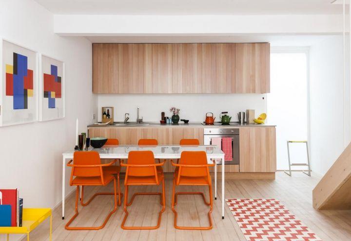 Le stampe dell'artista olandese Piet Mondrian e le sedie arancioni della cucina accendono un guizzo di colore nella zona giorno dell'appartamento londinese progettato da Studiomama. L'arredo su misura sfrutta al meglio lo spazio disponibile