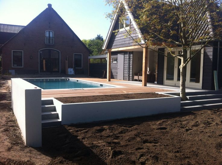 Zwembad tuin met sfeervolle invulling in Laren. Strakke lijnen worden ingevuld met warme materialen en weelderige beplanting. Under construction | Heart for Gardens.