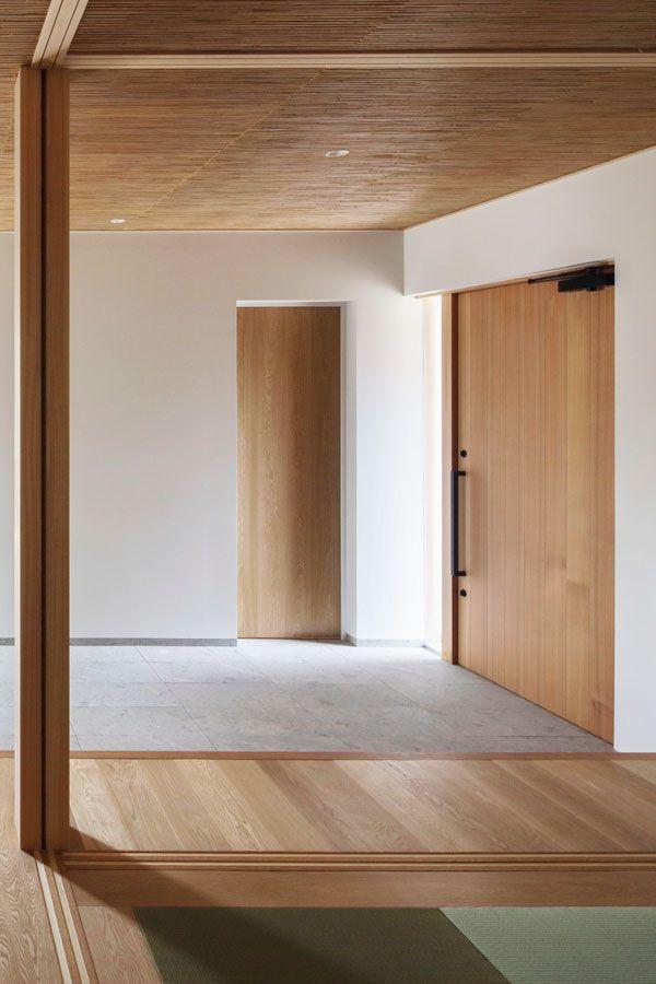 木製の大きなドアが印象的な土間空間 住宅 玄関 土間収納 家