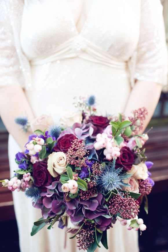 Has ivory roses, dark dahlias, dark hydrangea, thistle, a different fillers -good overall color pallete