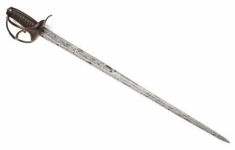 """J35B.- Espada de tropa de Infantería. España, Carlos IV, 1799. Guarnición de bronce, de concha frontal y otra de menor en el reverso; dos guardamanos unidos por un gavilán en """"S"""", galluelo y monterilla larga. Hoja recta, filo al exterior, lomo cuadrado en el primer tercio, doble filo a tres mesas en el resto. Marcada """"T"""" (inspección), """"R"""" coronada (propiedad del Rey), """"C. IV"""" (Carlos IV) / """"Y"""" (Infantería), """"To."""" (Toledo), """"1799. Long. total 83,5 cm; Hoja 70,5 cm; Anch base hoja 32 mm"""