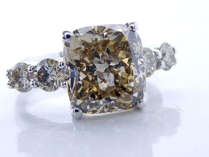 Ring metCushion geslependiamantchampagne kleurdiamant van 452 ct& 4 briljantenvan total 080 ct  Diamanten ring in 18K gouden set met 5.32 ct diamantenMidden geslepen cushion diamant Caraat: 4.52 ct Kleur: NATURAL champagneZuiverheid: I1Slijpsel: CushionAfmetingen van de steen:8.71X9.36X6.45 mmVersierd met 4 zijstenenKaraat: 080 CTKleur: NATURAL ChampagneZuiverheid: VS/ SISlijpsel: briljant Gewicht: 730 grRingmaat: 56/ 17.77mm Komt in luxe sieraden doosje. Aangetekende en verzekerde…