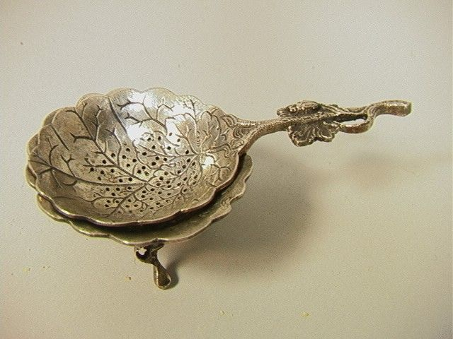 Silver Tea Strainer with stand, kind of looks like a leaf design.