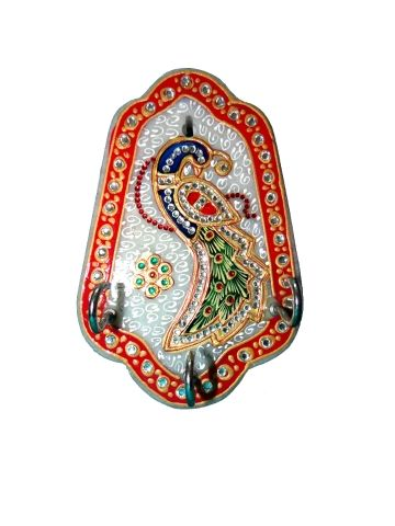 A masterpiece in marble. This attractive three hook key holder is made by glistening white Makrana marble. The borders of this artifact are lined with red and gold, embellished with kundan work. The central motif is a colourful Peacock(the Indian national bird) proudly displaying his iridescent plumage with beautiful colors, design and kundan work.   More visit at http://www.indyhaat.com