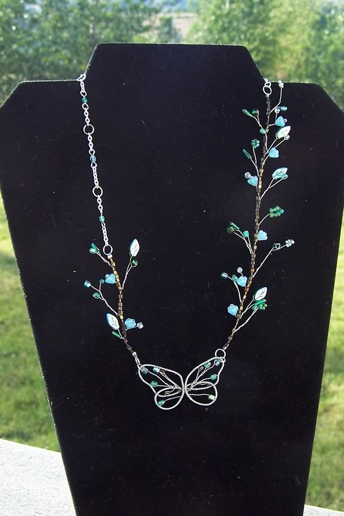 Butterfly Necklace by Laura Lattin - Wire wrapping & wire twisting, and, really, just a few beads (on a background of a single line of little beads that hide the wire). i like the asymmetry and the delicacy: Wirework, Flower