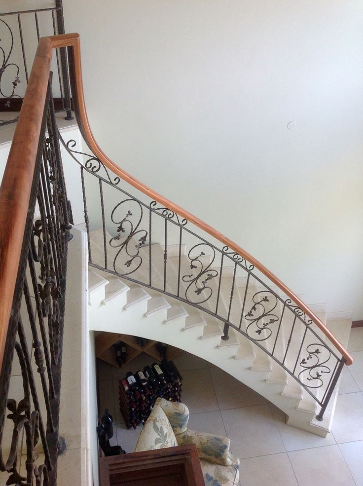 A beautiful stained meranti twist curve timber handrail on wrought iron balustrades