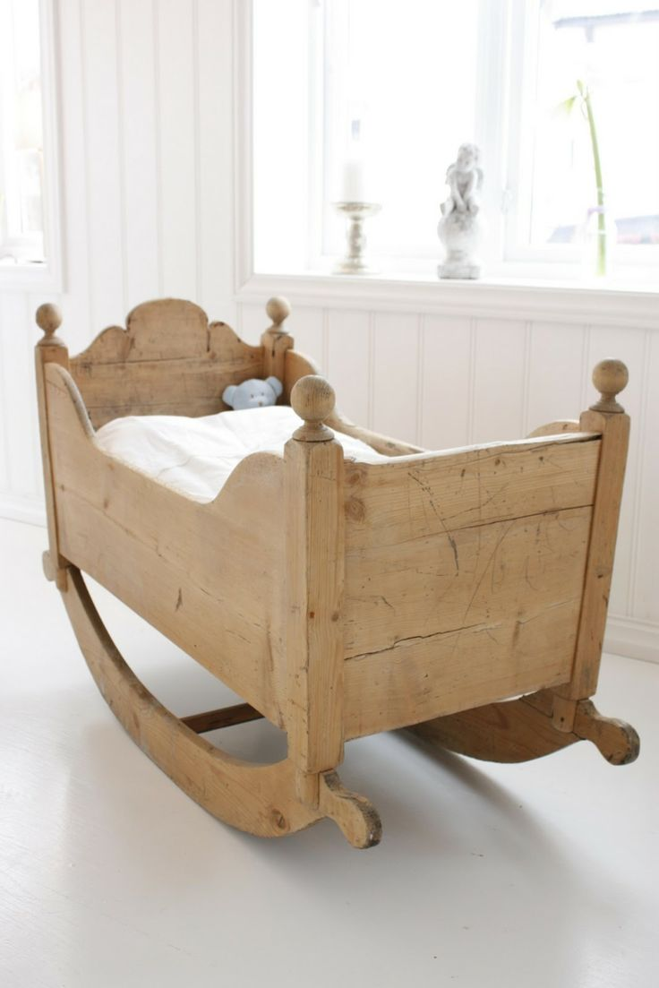 cuna de madera que se balancea en la habitación de bebé