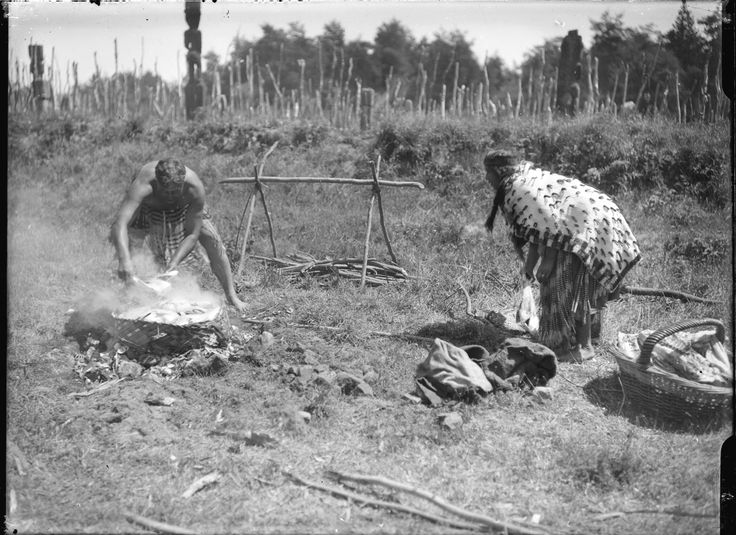 Showing an umu. A young Maori man is cooking a kite of fish on hot stones while a Maori woman looks on 1930's