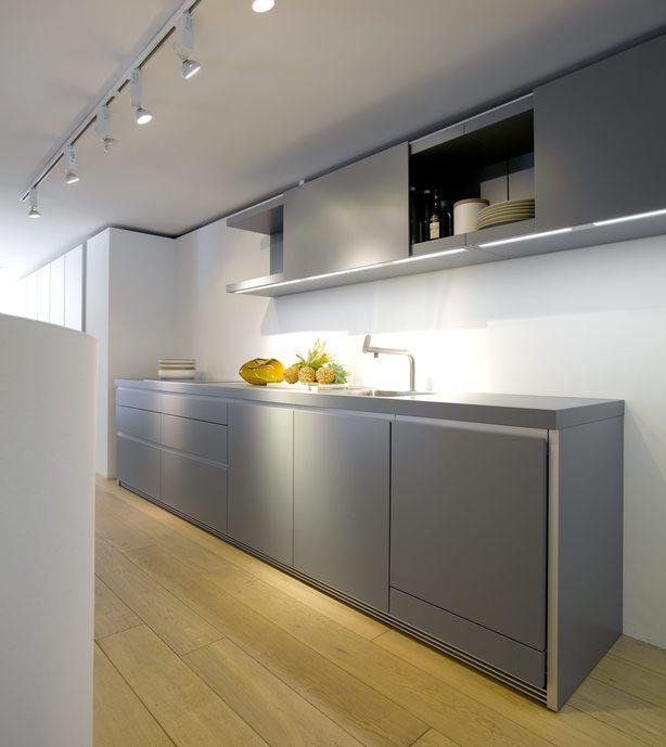Greeploze designkeuken in grijs. Het zachte grijs en de strakke belijning geven deze keuken een modern maar toegankelijk uiterlijk. De keukenkasten wil je op een bepaalde manier gewoon even voelen, aanraken, weten wat er achter zit. Boven de greeploze kasten ligt een prachtig keukenblad in dezelfde mooie grijze kleur. De bovenkastjes hebben een speelse vorm en zijn expres niet recht boven het aanrecht gehangen waardoor de hele keuken een mooie spanning heeft. bulthaup