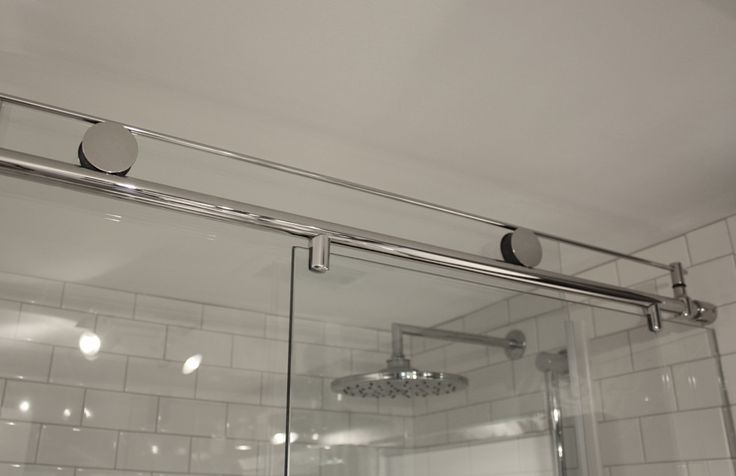 Custom glass doors on a barn door style roller system ensures a smooth and effortless glide while keeping the room open and allowing light to filter in easily. www.doorsandmore.ca