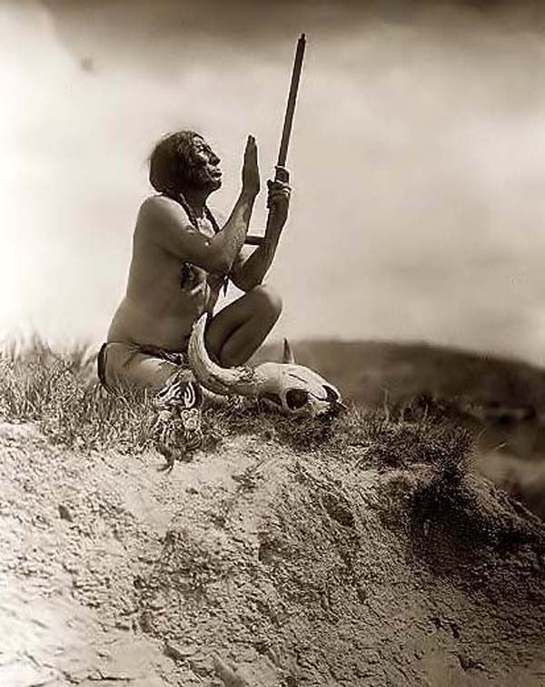 Slow Bull Praying to the Great Spirit. It was created in 1907 by Edward S. Curtis.    The photograph presents Slow Bull, squatting, wearing breechcloth, holding pipe with mouthpiece pointing skyward, buffalo skull at his feet.