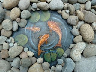 garden art : fish painted on a slate rock...surrounded by river rock