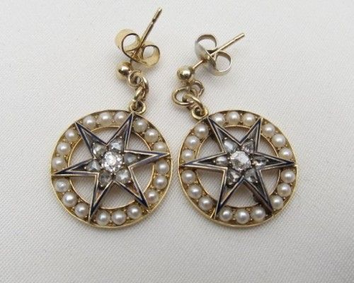 Circa 1870.  Victorian earrings each centered by a diamond starburst. Rose cut diamonds radiate from a beautiful old mine cut diamond. The starburst is outlined in subtle blue enamel. The stars are surrounded by delicate seed pearls. The earrings are 18KT yellow gold