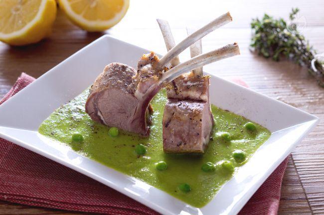 Il carrè di agnello su crema di piselli è un secondo piatto raffinato preparato con costine di agnello cotte in forno e servite su crema di piselli
