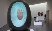 This is a sculpture by Barbara Hepworth. It looks like it is a rock. It is made by marble and is very polished. The da k colour on the outside contrasts against the light blue colour on the inside.