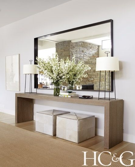 Contemporary neutral entry way design with oversized mirror and dual lamps and ottomans