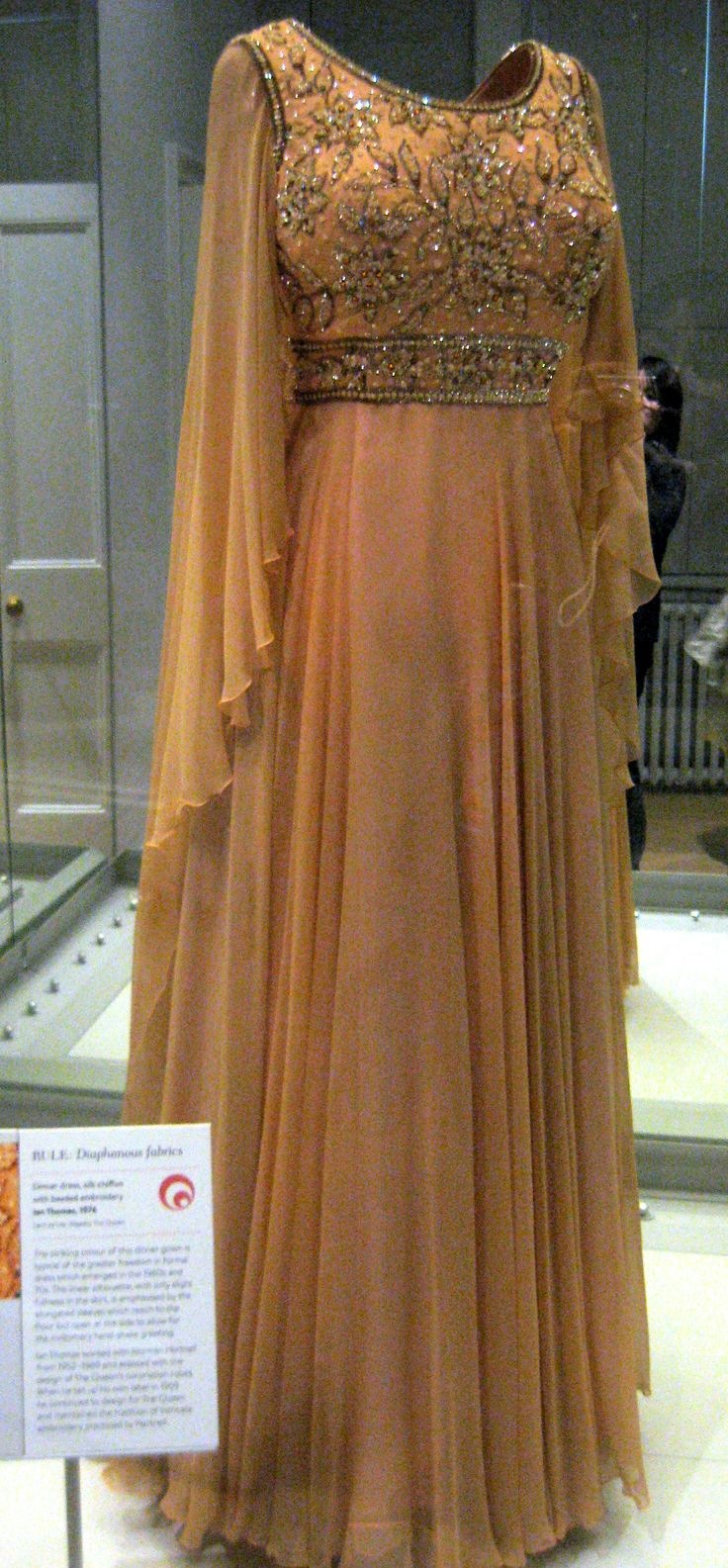 """1976 Dinner dress by Ian Thomas worn by Queen Elizabeth II at Kensington Palace, London - From the curators' comments: """"The striking colour of this dinner gown is typical of the greater freedom in formal dress which emerged in the 1960s and 70s. The linear silhouette, with only slight fullness in the skirt, is emphasised by the elongated sleeves which reach to the floor but open at the side to allow for the customary hand-shake greeting."""""""