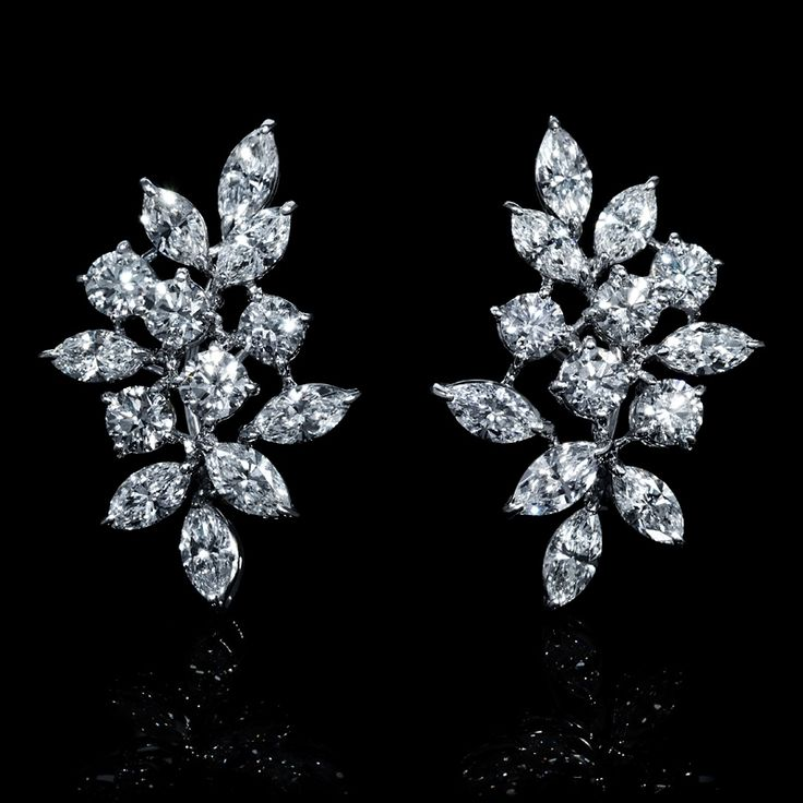 These lavish pair of 18k white gold cluster earrings, designed in Italy, feature 10 round brilliant cut and 16 marquise cut white diamonds of F color, VS2 clarity and excellent cut and brilliance, weighing 8.01 carats total.