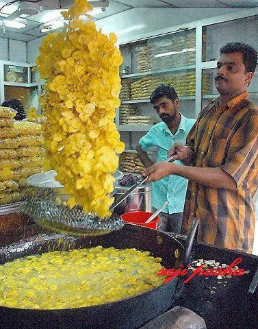 You like potato chips? why not to try other stuff...A man frying banana chips in…