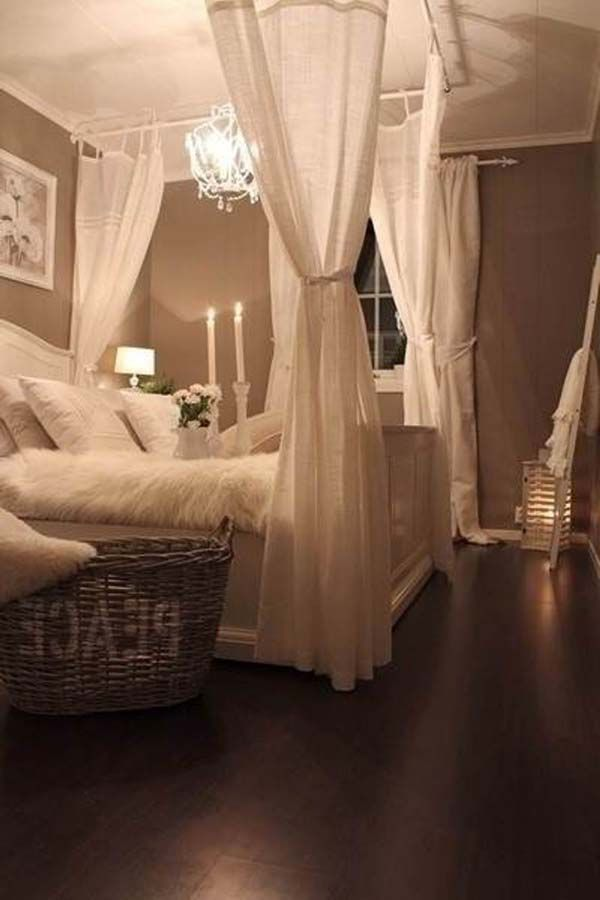 That bed all white plush w/ sheer canopy. Cherry wood floor and neutral light briwn walls candles and big bedrior canvas pic above bed, tufted white head board, shelf, white and painted/ stenciled furnitue, vanity section. Storage, curtains luxe. Teinkle lights. Tv mounted