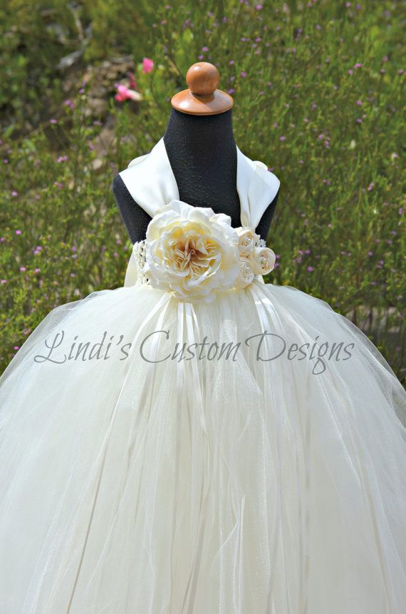 Simply beautiful! Our flower girl dress features an ivory ambiance with a matte and shimmer tulle blend. This listing is for the pictured style tulle tutu dress for flower girls, pageants, and special occasions in sizes baby up to a 6/7 yr old or not to exceed a chest measurement of 23.  Top portion of our gown features an ivory stretch crochet band for comfort. Each strand of tulle is hand tied tightly for the fullness shown in photos. Our dress features a quadruple layer of tulle we us...