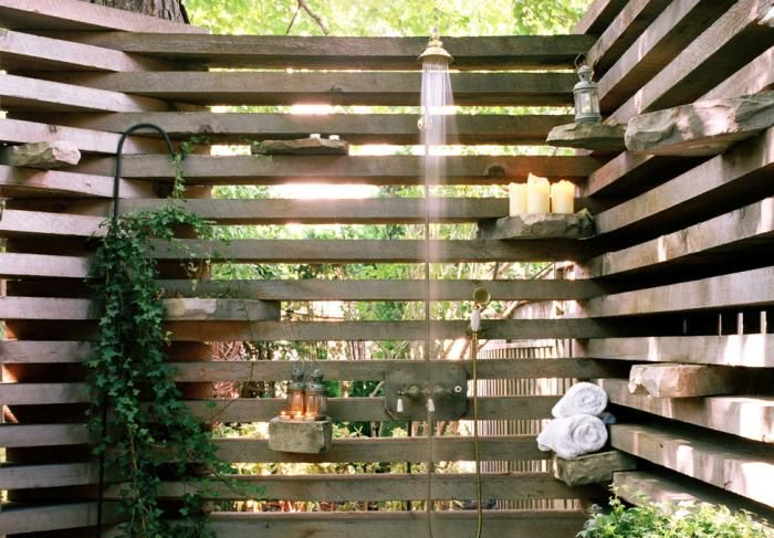 Privacy screen: stacked-slat walls create support for cantilevered ledges of flat stones. This one is a shower.