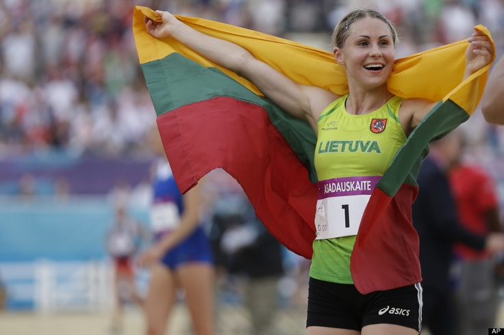 Laura Asadauskaite, of Lithuania, celebrates with her national flag after she won the gold medal in the women's modern pentathlon, at the 2012 Summer Olympics, Sunday, Aug. 12, 2012, in London.