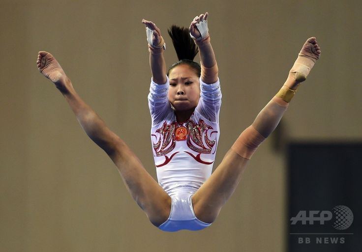 China's Chen Siyi performs on the uneven bars during the women's qualification round at the Gymnastics World Championships in Nanning, in China's southern Guangxi province on October 6, 2014. (c)AFP/Greg BAKER ▼13Oct2014AFP|【写真特集】カメラがとらえた世界体操のワンシーン http://www.afpbb.com/articles/-/3028472
