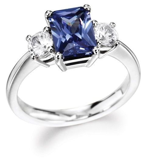 Our dazzling Emerald Cut and Round Trilogy Engagement Ring shown set with a Sapphire & Diamonds