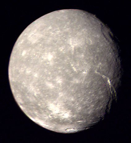 Titania is Uranus' largest moon and the 8th largest moon in the Solar System w/ a diameter of 981-mi. This photo of Titania's southern hemisphere was taken on 1/24/ 1986 by Voyager 2. Along the terminator are visible the moon's largest known impact crater, Gertrude, at upper right and several enormous canyon-like grabens (the Messina Chasmata above, Belmont Chasma near bottom) at lower right