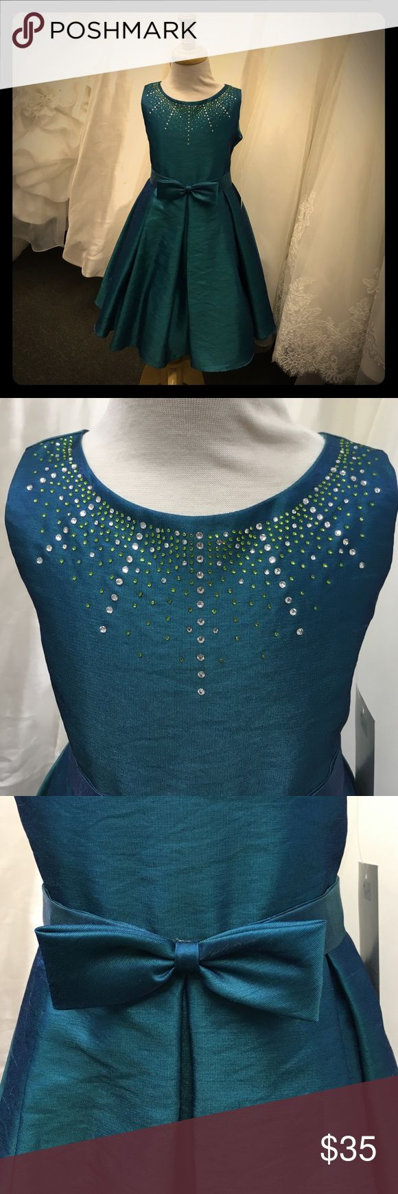 NWT Julia Lee dress style #J-1222 NWT beautiful iridescent teal dress with light green and silver beading along neckline with bow at waist and tie in the back. Offers welcomed Julia Lee Dresses Formal