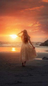 Kobieta na plaży w zachodzącym słońcu