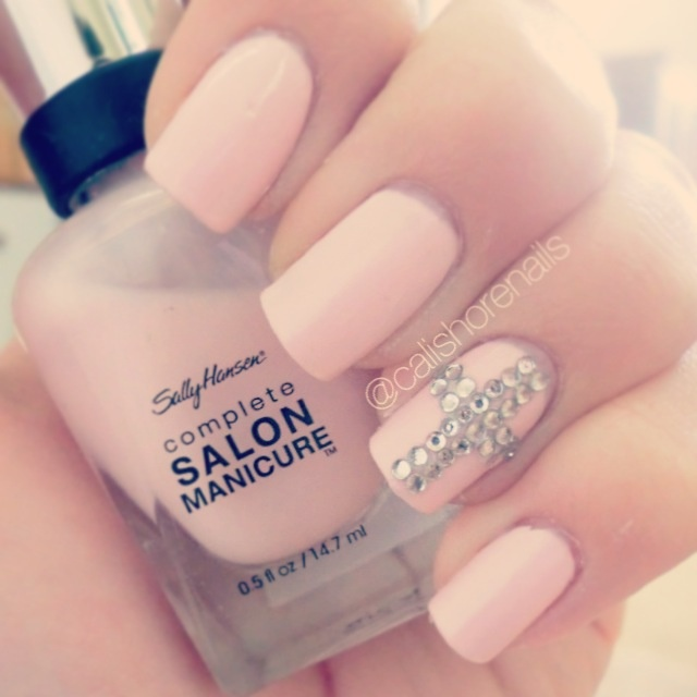 Baby pink nails with a gem cross on the ring finger ...